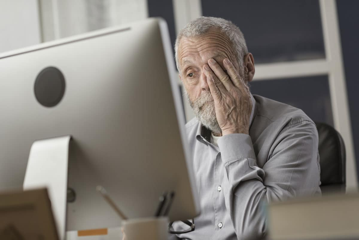 Cogntitive Impairment - senior looks at computer screen with frustration