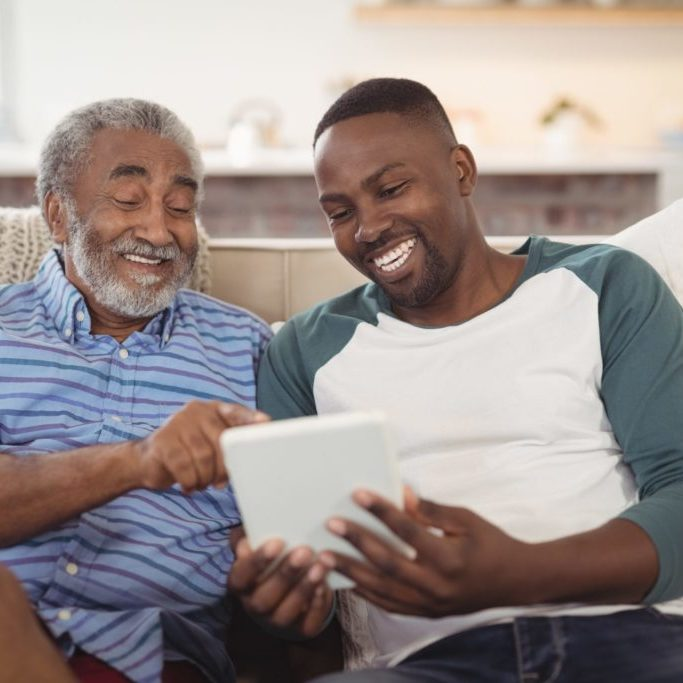 Father and son showing user interface design for seniors using tablet on couch