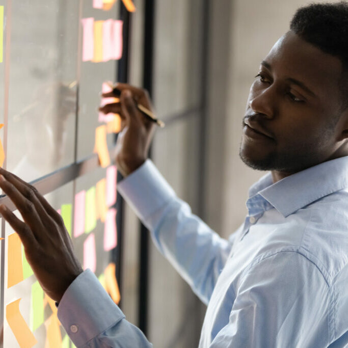 Black man organizes a wall of sticky notes
